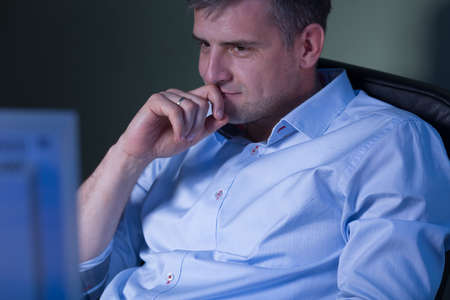 night shift: Tired man watching movie during night shift at work Stock Photo