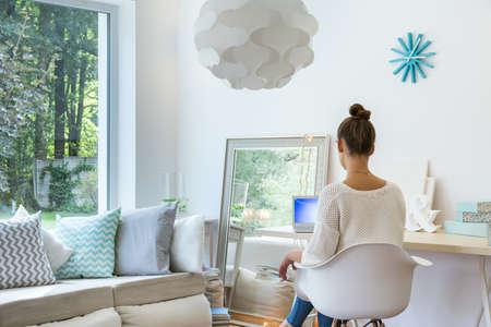 homelike: Girl sitting at desk in sunny room Stock Photo