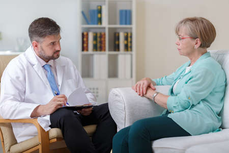 talking: Elder woman talking with psychologist about her problems Stock Photo