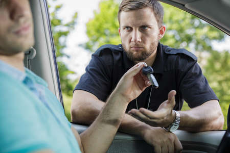 giving back: Drunk driver giving back the keys to the police officer