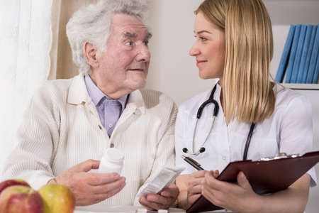 senescence: Image of young doctor examining male patient of nursing home Stock Photo