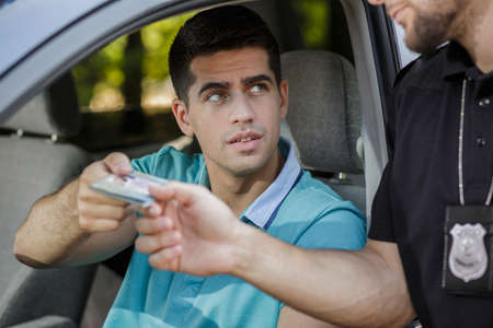 driving a car: Police officer giving back documents to young man