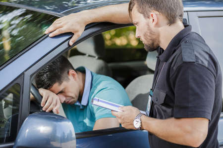 traffic officer: Sad young man in car fined by police officer Stock Photo