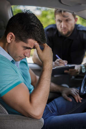 fined: Young man fined by policeman for fast driving Stock Photo
