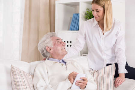 senescence: Picture of helpful granddaughter visiting her grandfather in rest home