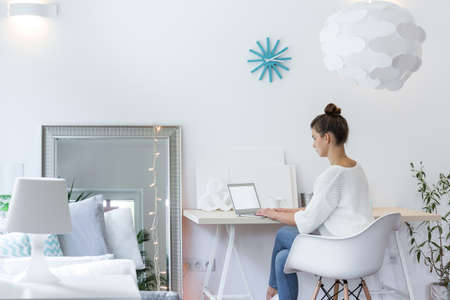 Girl working on laptop in white room