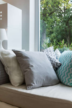 homelike: Cosy modern pattern pillows on comfortable couch Stock Photo