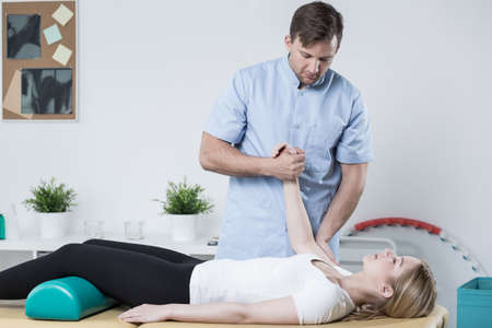Image of handsome physiotherapist working with female patient Stock Photo