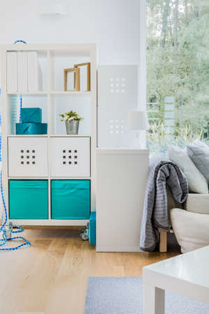homelike: White minimalist rack in white living room Stock Photo