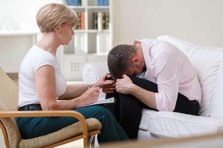 terapia psicologica: Hombre de mediana edad llorando durante la terapia psicológica