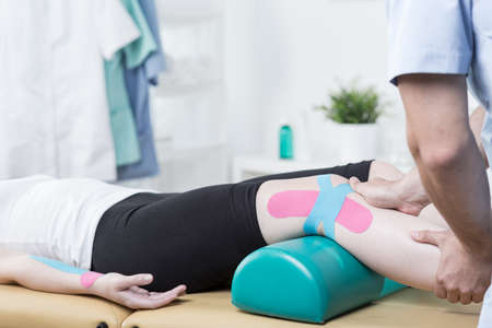 alternative therapies: Photo of patient with elastic therapeutic tape during exercises