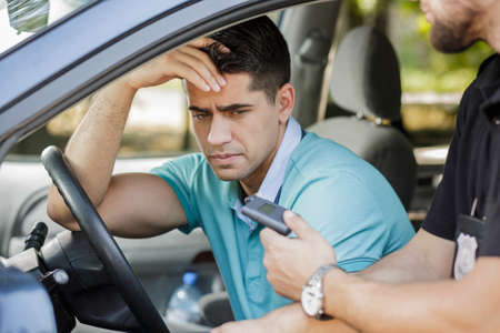 and the horizontal man: Drunk man caught in car by police officer Stock Photo