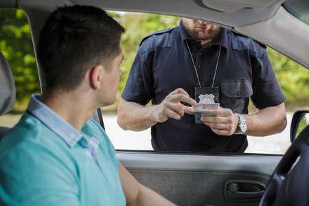 Politieagent te kijken naar jonge bestuurder het rijbewijs Stockfoto