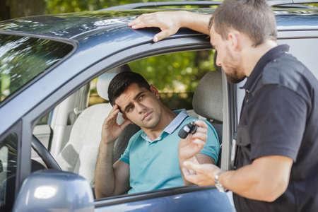 policier: Sad jeune homme donnant ses clés de voiture à policier