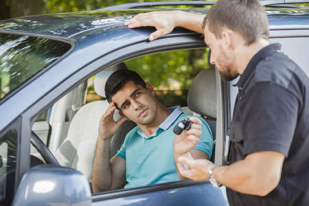 officer: Sad young man giving his car keys to policeman Stock Photo