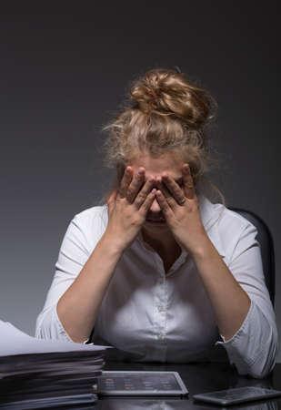 work stress: Image of depressed female mobbing victim at work