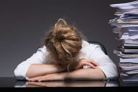 sleeping on desk: Image of overworked woman sleeping on desk at her workplace Stock Photo