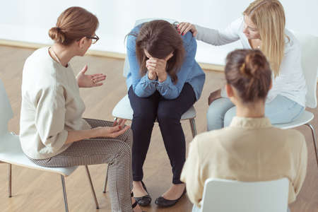 Support: Young despair woman crying during group therapy Stock Photo
