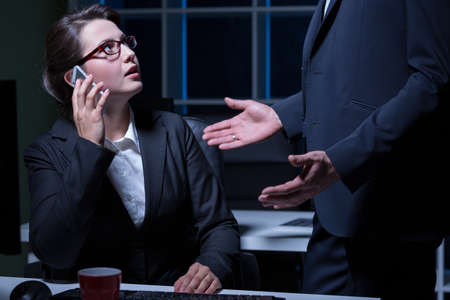 to the secretary: Boss and scared secretary talking on the phone Stock Photo