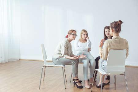 El entrenador y el grupo de apoyo durante la terapia psicológica Foto de archivo - 46452439