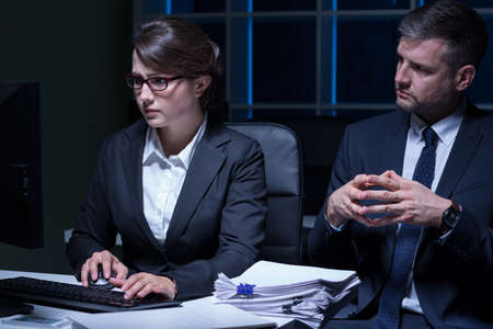 overworking: Horizontal view of office workers doing overtime Stock Photo