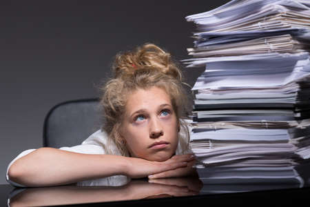 mental disorder: Portrait of depressed girl overhelmed by paperwork