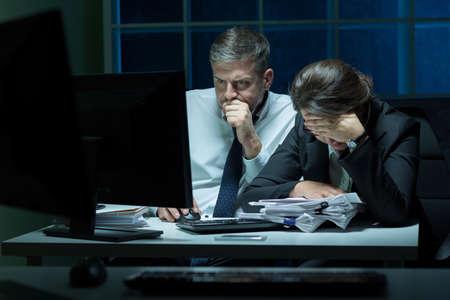 empleados trabajando: Empleados con exceso de trabajo que trabajan por la noche en la oficina