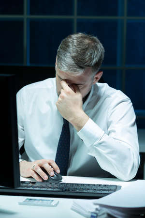 cansancio: Imagen de hombre de negocios con exceso de trabajo que trabaja horas extras Foto de archivo