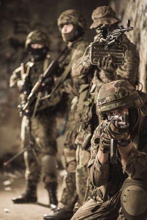 Fully equipped military men in camouflage uniform