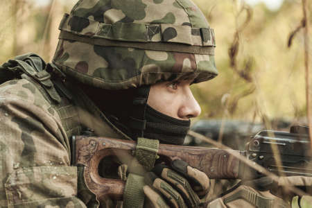 military training: Military woman with a rifle lying in the grass