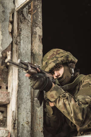 proving: Young soldier with pistol aiming at somebody Stock Photo