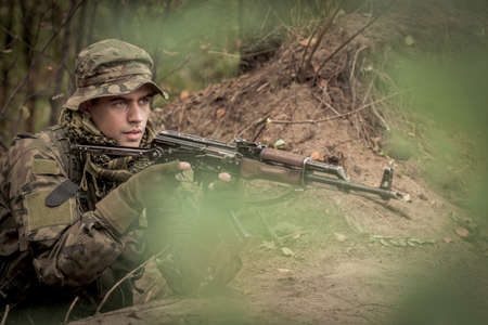 weapons: Sniper in military uniform with automatic weapon