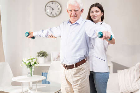 care at home: Physiotherapist is taking care of her old patient Stock Photo