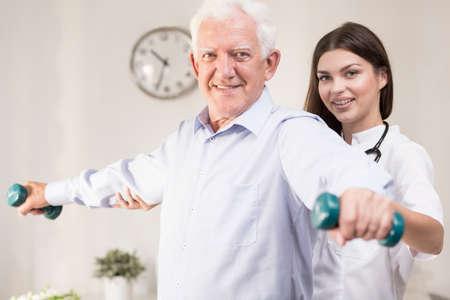 actividad fisica: Senior est� entrenando con el joven fisioterapeuta Foto de archivo