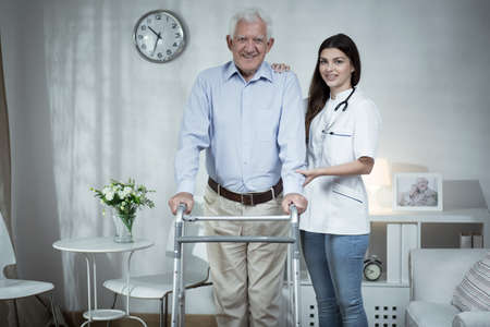 home nursing: Young doctor is helping elder and lonely man