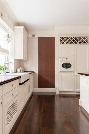 worktops: Picture of modern white furnished kitchen with brown floor