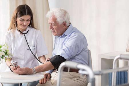 persona de la tercera edad: Enfermera joven está tomando la sangre mayor de hombre Foto de archivo