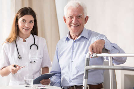 patient care: Young doctor is visiting her old patient