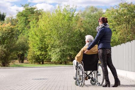 empujando: discapacidad superior al hombre y ayudante en el parque