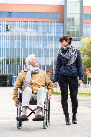 persona de la tercera edad: Hombre mayor en una silla de ruedas en un paseo