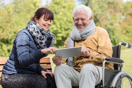 Lachende gehandicapte man en verzorger met een tablet