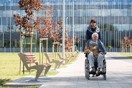 empujando: Trabajador Social y hombre discapacitado en una caminata