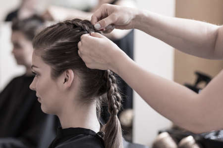 hair style: Female hairdresser is braiding young womans hair