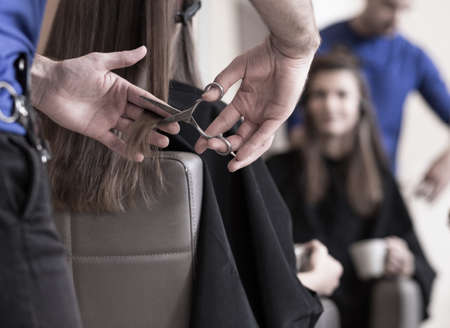 Hairdresser is cutting young woman's hair