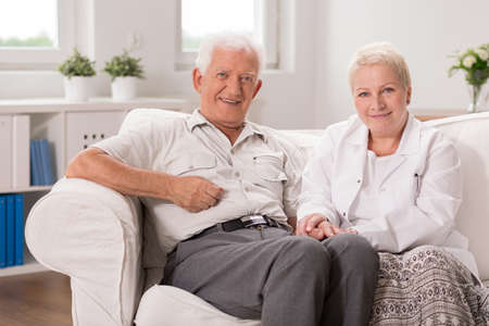 old man: Kind nurse is holding her patients hand