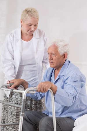 Verpleegster helpt oude man om op te staan