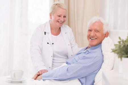 Verpleegster zorgt voor haar oude patiënt Stockfoto