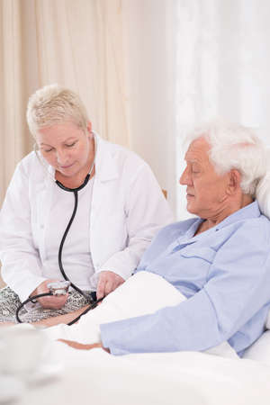 patient in hospital: Nurse is checking the pulse of her patient