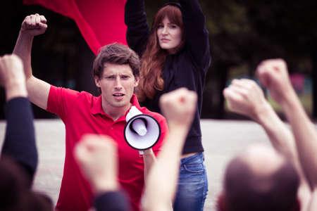 megafono: Imagen de hombre joven con megáfono rebelde durante la protesta callejera