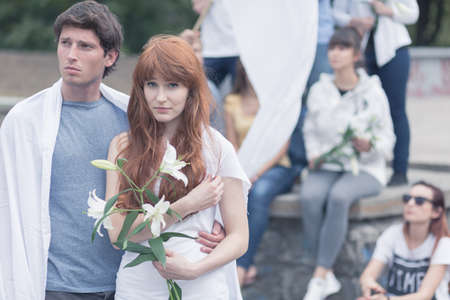 white lilly: Image of protesting man and woman with white lilly Stock Photo